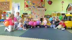 Zdjęcie grupowe z balonami i plakatem Dzień Przedszkolaka