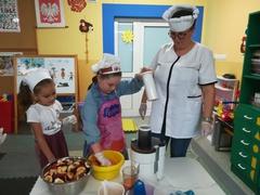 dwie dziewczynki i nauczyciel przy sokowirówce
