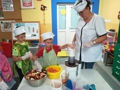 dwóch chłopców i nauczyciel przy sokowirówce