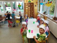 dzieci przy stolikach piją sok