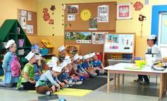 dzieci w fartuszkach i czapkach siedzą na macie