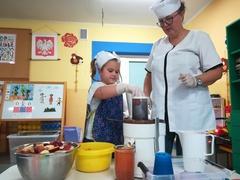 dziewczynka i nauczyciel przy sokowirówce
