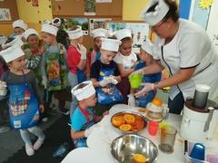 nauczyciel zapoznaje dzieci z wyciskarkami do owoców