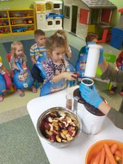 Dziewczynka wrzuca jabłko do sokowirówki
